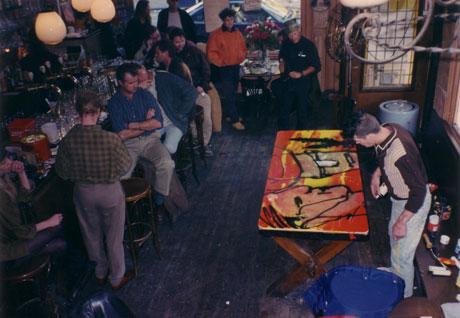 Herman Brood beschildert de stamtafel van café De Toog, links van hem manager Koos van Dijk, 1995