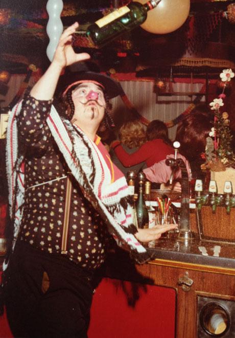 Hazes jonglerend met een fles jenever achter de bar van café de Krommerdt, begin jaren '70