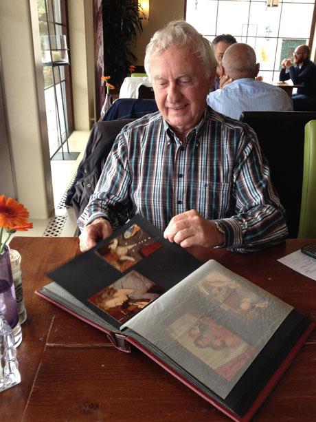 Klaas Veen met één van zijn plakboeken vol foto's van zijn tijd als cafébaas