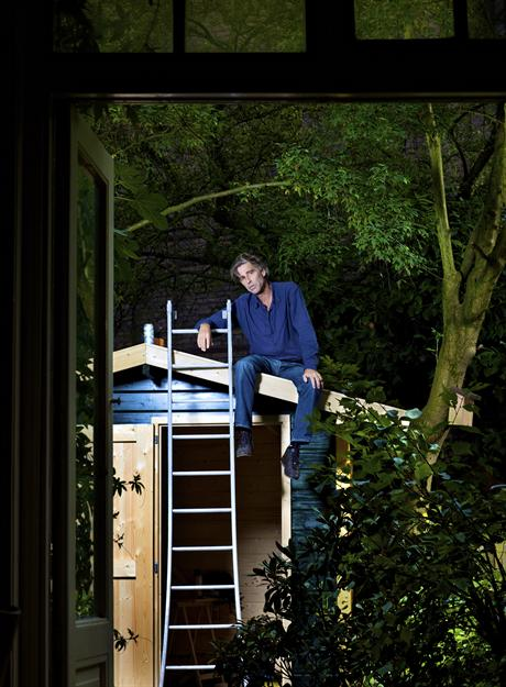 Maarten van Roozendaal bij/op het schuurtje in zijn tuin aan de Tweede Kostverlorenkade waar hij veel van zijn liedjes schreef (Foto: Jacqueline de Haas)