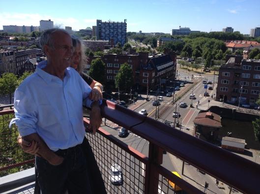 Bewoners Paul Schouten en Margot Vos op het balkon van hun huis, op de achtergrond het Surinameplein
