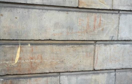 De teksten en tekeningen die Coenraad van Beuningen 327 jaar geleden met zijn eigen bloed op de buitenmuren van Amstel 216 kalkte. De tekens zijn links en rechts naast de voordeur te zien op ooghoogte